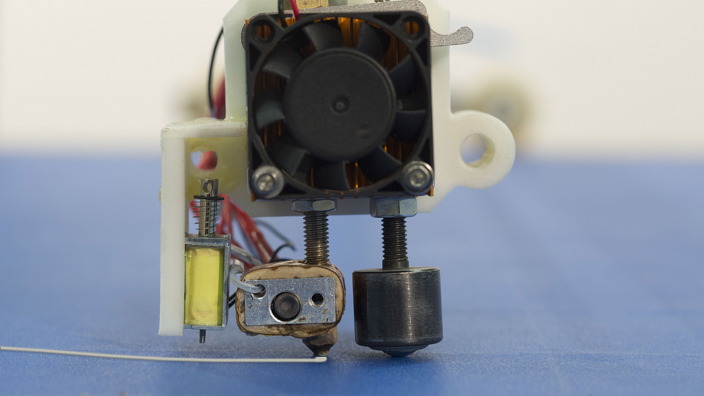 a close-up picture of the head of the device. You see from left to right a scraper to remove contents, an extruder which prints lines and a ball caster that prevents the extruder from hitting the board. On top of that is a large ventilator to cool the hea